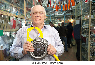 man holds   clutch  in  auto parts store