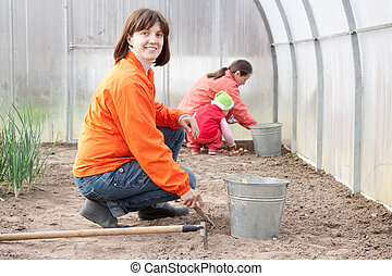 family sows seeds  at greenhouse
