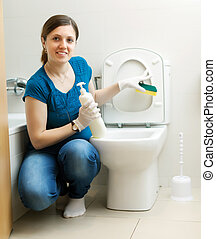 Smiling housewife cleaning toilet bowl with sponge in...