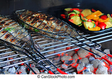 Grilled Fresh Fish (Trout) on the barbecue next to a pan of...