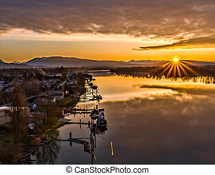 Sunrise Star Next To River With Boats - This sun star rises...