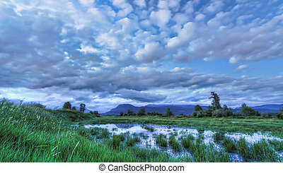 Blue Landscape with Dramatic Clouds Mountain and Water