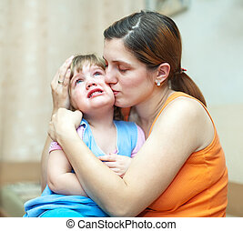 woman calms daughter - woman calms her daughter in home....