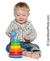 Cute baby boy is playing with toys