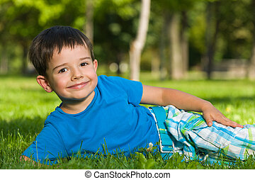 Cute boy in blue shirt on the grass - A cheerful boy in blue...