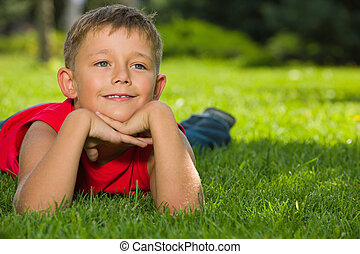 Dreams on the green grass - A thoughtful boy in red shirt is...