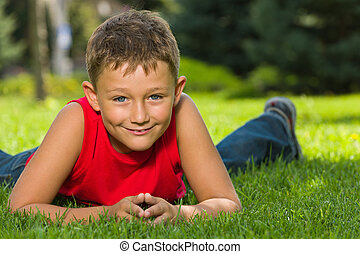 Great on the grass! - A cheerful boy in red shirt is lying...