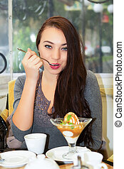 Pretty young brunette having meal in a cozy cafe