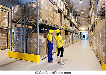 Workers in warehouse - Workers in hard hats standing in...