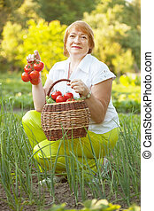 mature woman with vegetables in garden