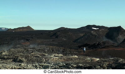 Tourist walking trough volcanic area in Iceland