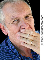 Hand On Mouth Senior - Wary senior male with hand on mouth...