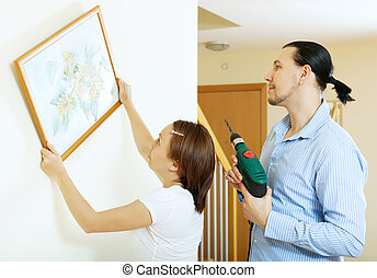 couple hanging the art picture on wall