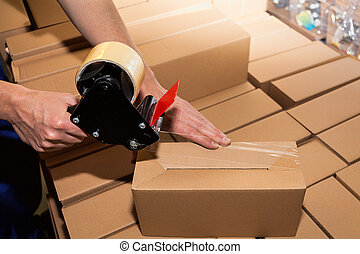 Packing a carton boxes - Worker using adhesive tape to close...
