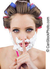 Secretive woman in hair curlers posing with shaving foam and...