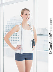 Cheerful sporty woman holding skipping rope in bright sports...