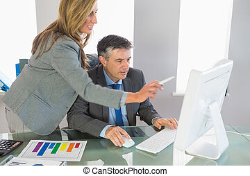 Serious blonde businesswoman explaining something on the computer to a concentrated mature businessman at office