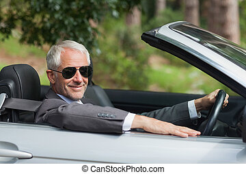 Smiling mature businessman driving classy cabriolet on sunny...