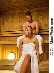 Man giving his girlfriend a neck massage in sauna wearing...