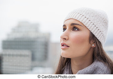 Pensive cute woman with winter clothes on posing