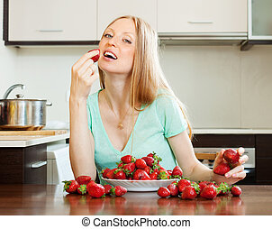 long-haired woman eating strawberry in home kitchen