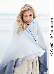 Fashion blonde woman covering herself in a blanket on the...