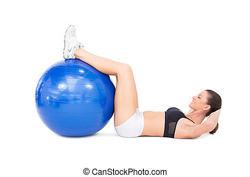 Fit woman developing her abs using exercise ball on white...