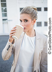 Gorgeous stylish businesswoman drinking coffee outside on...