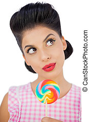 Wondering black hair model holding a colored lollipop