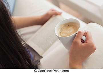 Woman lying on the sofa reading a book holding her coffee