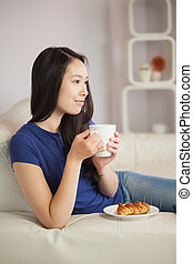 Young asian woman sitting on the sofa having coffee with a pastry in living room at home