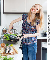 Positive girl with raw fish in frying pan at domestic...