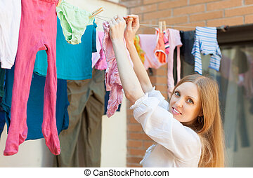 Girl hanging clothes on clothesline - Girl hanging clothes...