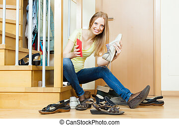 Happy woman cleaning footwear - Happy woman sitting on...