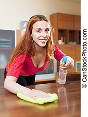 Happy long-haired girl in red dusting table - Happy...