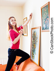 woman in red hanging   picture