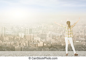 Young woman with stretched arms looking at city - Young...