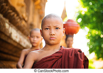 Young Buddhist monks walking morning alms in Old Bagan,...