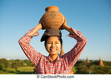 Asian traditional female farmer carrying clay pot - Portrait...