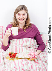 Happy woman enjoying breakfast in bed