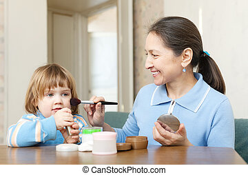 mature woman putting facepowder on little girl - Smiling...