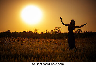 Silhouette of a dancing young girl in dress against the sunset sky