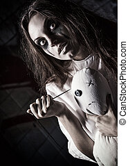 Horror style shot: scary mad girl with moppet doll and...