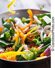 vegetables falling into a stir fry wok