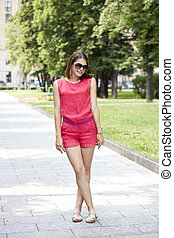 Street fashion Young woman in red shorts and a blouse -...