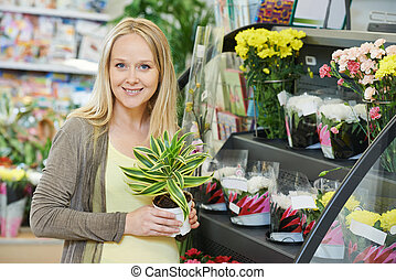 Woman shopping flower in store - Young smiling woman buyer...