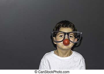 Oversized Clown Glasses - A young boy wearing a clown nose...