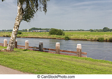 Canal with wooden bollards in typical Dutch countryside