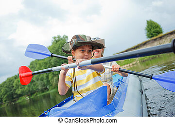 Family kayaking - Happy young boy with mother paddling kayak...