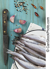 Cooking fish - A plate with fish on the kitche table and...
